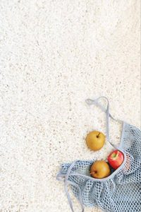 apples in a blue mesh bag laying on white carpet