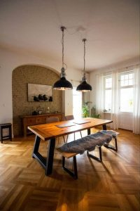 dining room with wood hardwood, a wood table, and accent wall