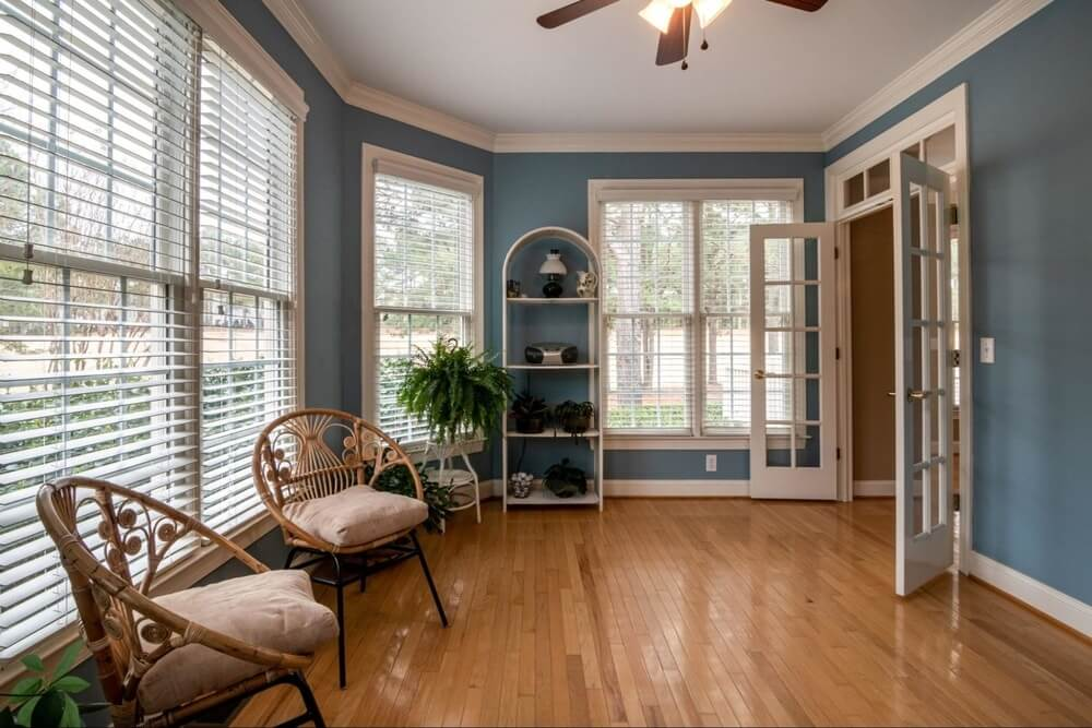a room with blue wallpaper, large windows, two chair, and a hardwood floor